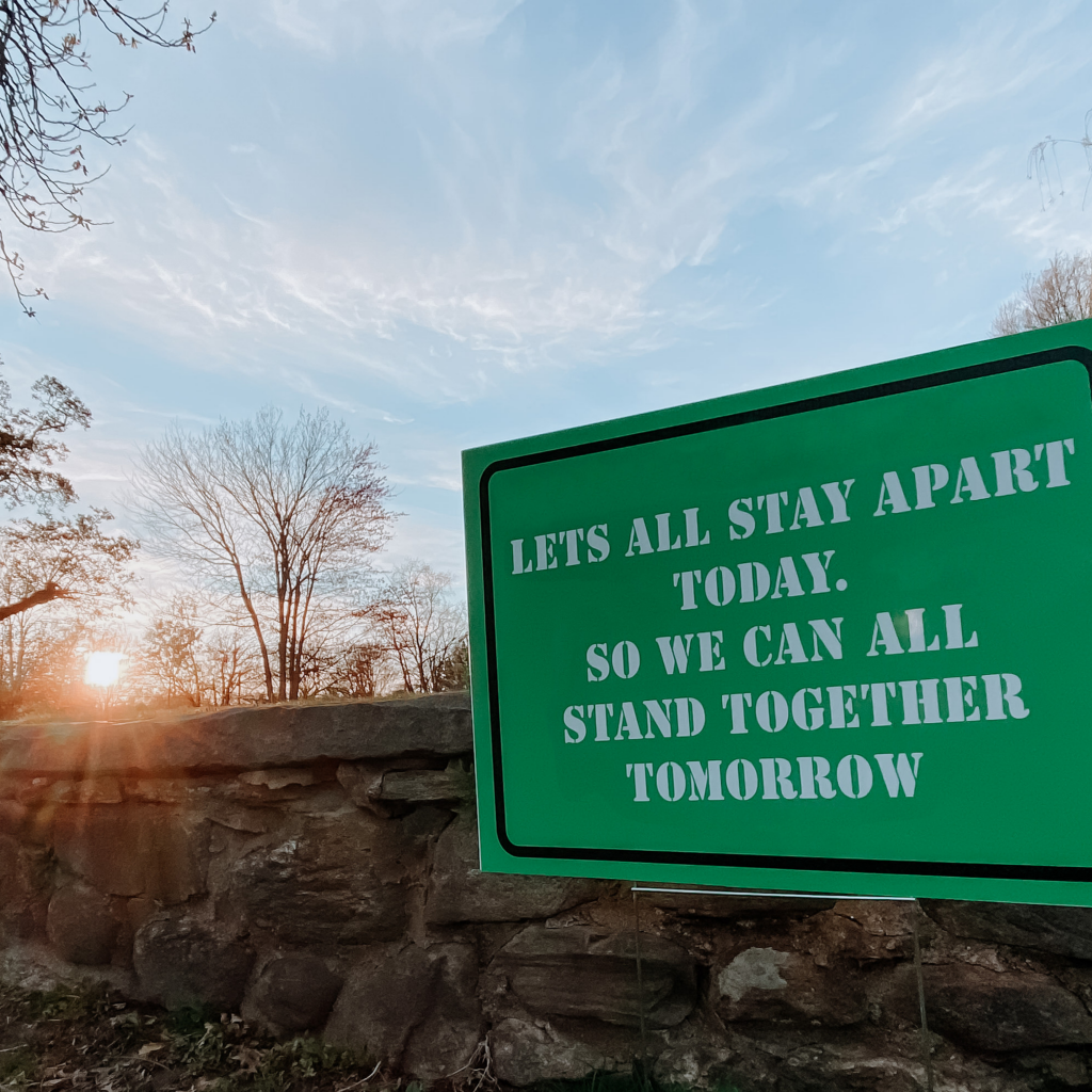 Green sign in front of a manmade rock wall that says Let's All Stay Apart Today. So We Can All Stand Together Tomorrow