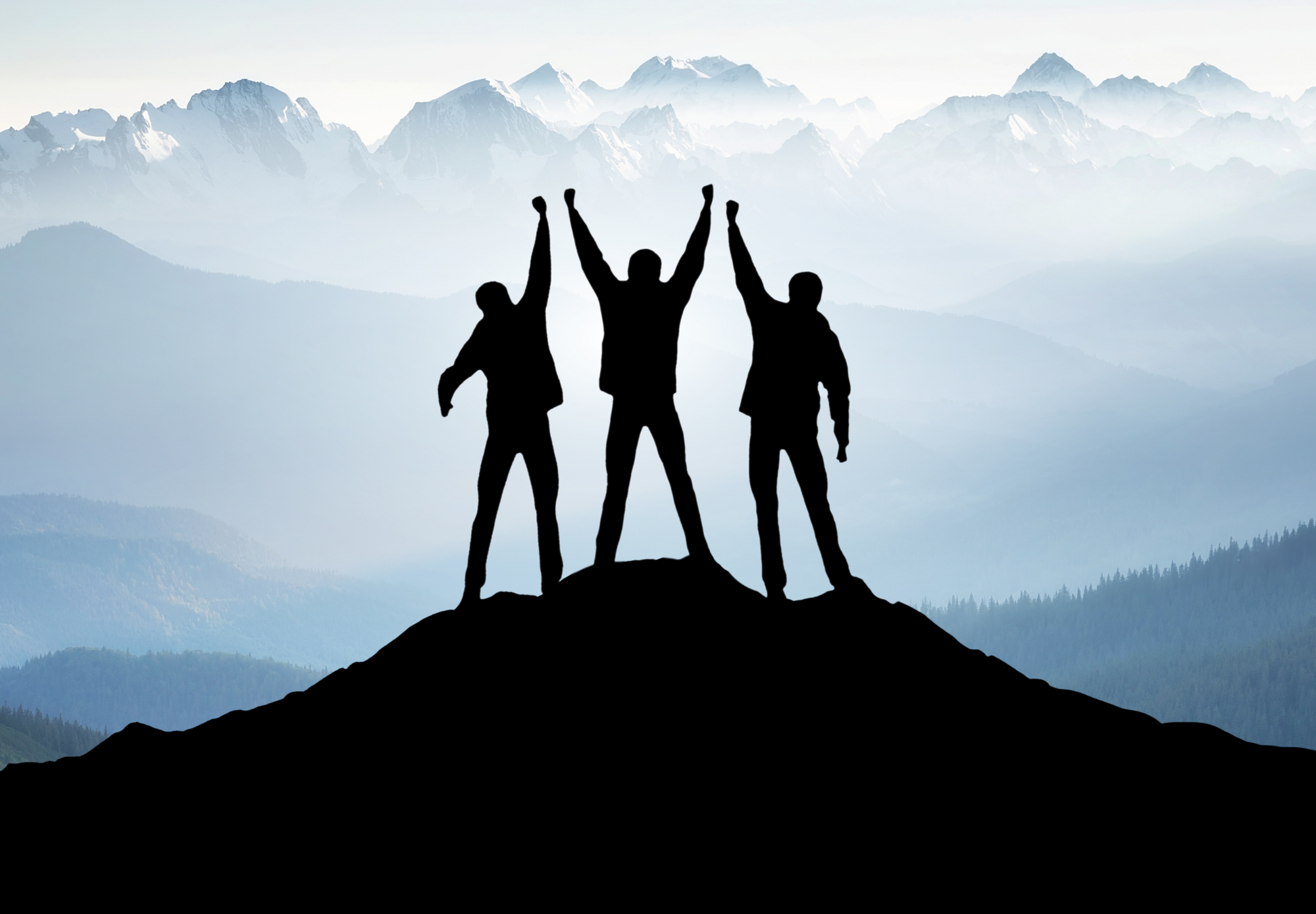 Three men with arms raised at top of summit with mountains in the background